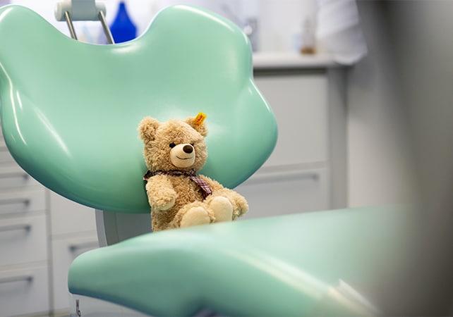 Teddybär sitzt auf türkisfarbenem Behandlungsstuhl