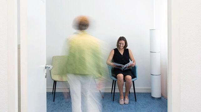 Frau sitzt im Wartezimmer und liest Zeitschrift während neue Person ins Wartezimmer tritt